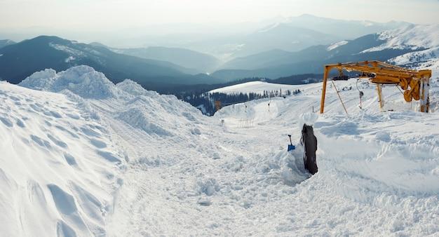 Remontée mécanique enneigée et paysage de montagne derrière