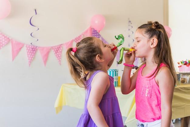 Remorquer mignonnes petites filles soufflant corne de fête
