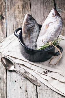 Remorquer le poisson cru de la dorade au romarin