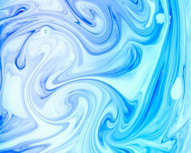 Remous de peinture dans un liquide de couleur bleue
