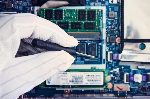 Remplacement de la mémoire dans l'ordinateur portable, dans l'un des centres de service pour la réparation des ordinateurs portables. la main dans un gant blanc tient un tournevis sur le fond de l'ultrabook moderne démonté.