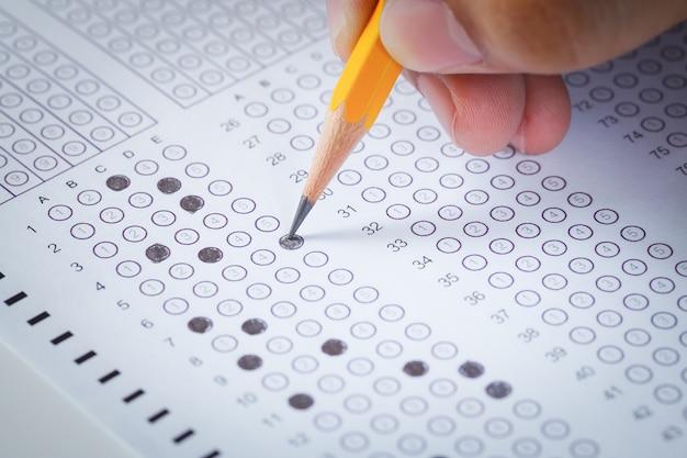 Remplir à la main une feuille d'ordinateur en papier carbone examen et un crayon