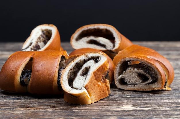 Le remplissage de graines de pavot et d'œufs dans un petit pain à dessert avec un pain frais avec une garniture noire de graines de pavot
