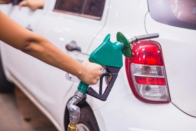 Remplissage de voiture avec de l'essence à la station-service et pompe à essence remplissant la buse de carburant dans le réservoir de carburant de la voiture