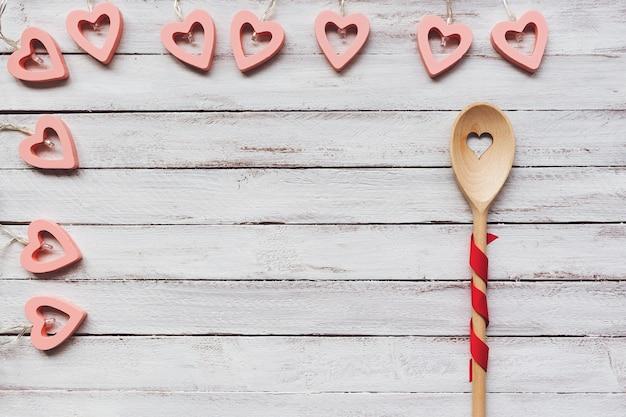 Remuer la cuillère et la décoration de coeurs sur fond de bois
