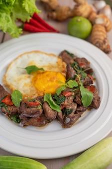 Remuer le foie de basilic frit avec des œufs sur le plat dans une assiette blanche.