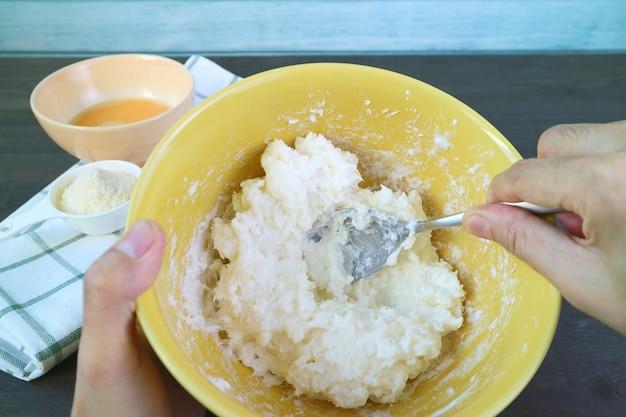 Remuer à la main le mélange dans un bol avec une cuillère pour la cuisson du pain au fromage brésilien