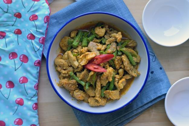 Remuer le porc frit avec de la pâte de curry et des haricots verts