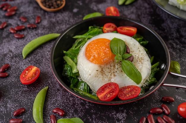 Remuez le chou frisé et l'œuf frit dans une poêle.