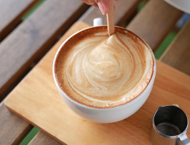 Remuez à la main café latte chaud avec sur la table en bois.