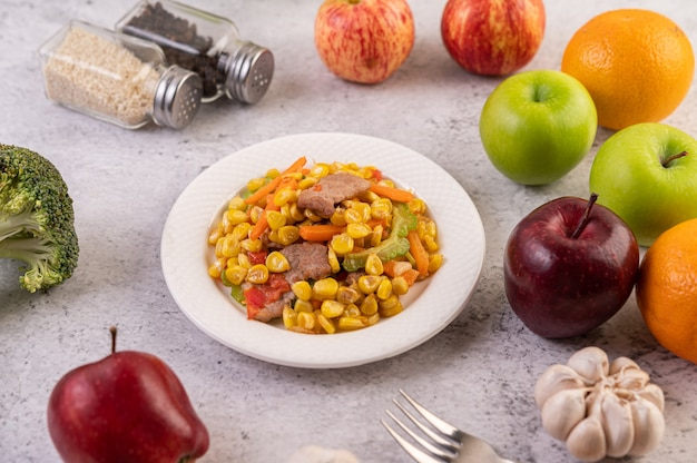 Remuez le maïs et les carottes, mettez le porc dans l'assiette sur l'assiette en bois.