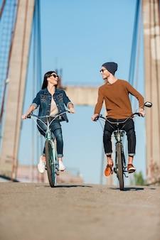 Rencard parfait. beau jeune couple faisant du vélo le long du pont et se regardant avec le sourire