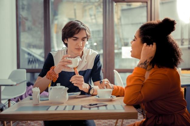 Rencontre chaleureuse. un garçon et une fille buvant du thé dans le café