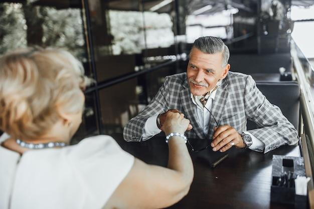Rencontre de deux seniors amoureux, ils sont assis à la terrasse d'été et se regardent, elle sympathise avec lui