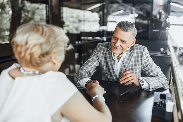 Rencontre de deux seniors amoureux, ils sont assis à la terrasse d'été et se regardent