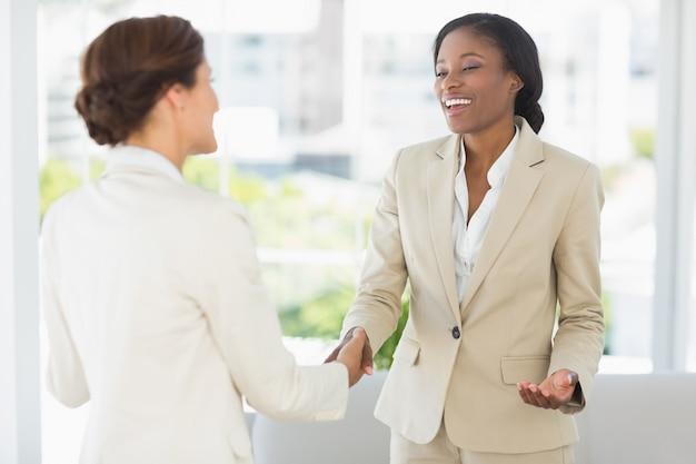 Rencontre de femmes d'affaires heureuses et serrant la main