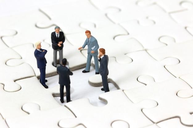 Rencontre d'homme d'affaires miniature sur une pièce du puzzle perdu.