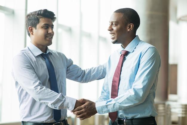 Rencontre joyeuse de jeunes entrepreneurs avec un partenaire commercial