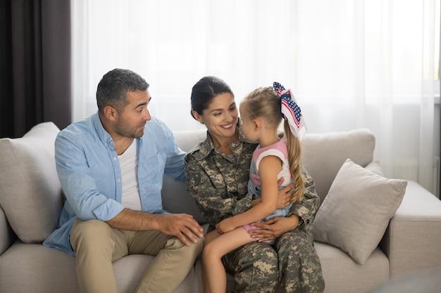 Rencontre avec leur mère. mari et fille rencontrant leur mère servant dans les forces armées à la maison