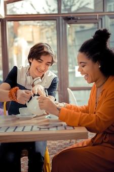 Rencontre avec le meilleur ami. les amis rient et boivent du thé ensemble