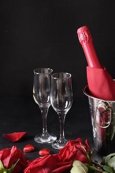 Rencontre romantique avec du vin mousseux froid, des bonbons et des roses rouges sur fond noir. célébration pour la saint valentin. format vertical.