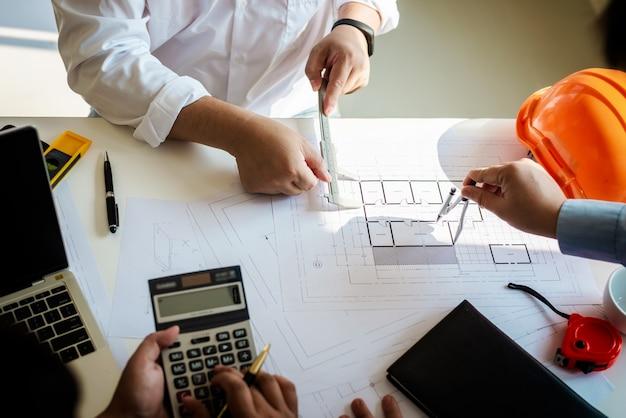 Rencontrer des gens avec des plans de construction de travail d'équipe architecte