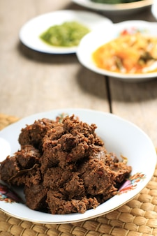 Rendang padang. ragoût de boeuf épicé de padang, indonésie. le plat est arrangé parmi les autres menus de warung nasi padang.