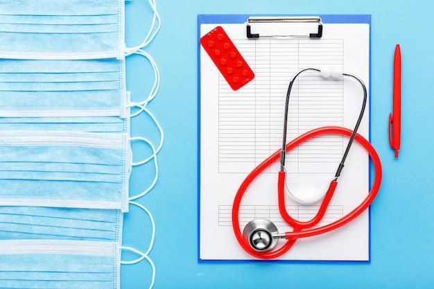 Rendez-vous médical. stéthoscope rouge, masques hygiéniques médicaux, comprimés, documents médicaux sur le lieu de travail des médecins en clinique.