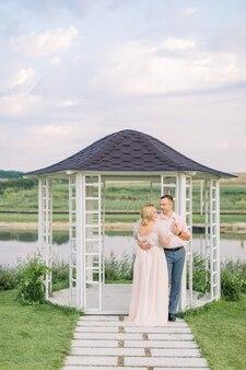 Rendez-vous romantique au bord de l'étang. heureux couple d'âge mûr, homme et femme dans des vêtements élégants, debout près d'un belvédère en bois sur la rive du magnifique lac
