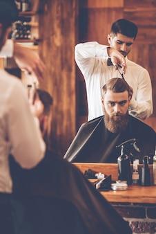 Rendre la coupe de cheveux parfaite. jeune homme barbu se coupe les cheveux par le coiffeur alors qu'il était assis sur une chaise au salon de coiffure devant le miroir
