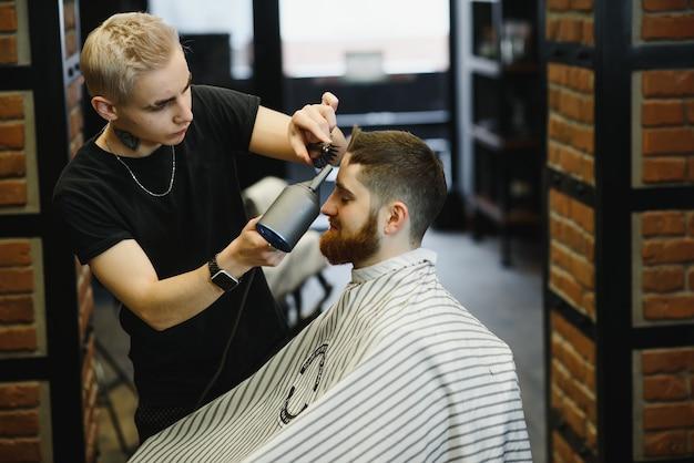 Rendre la coupe de cheveux parfaite. jeune homme barbu se coupe de cheveux par le coiffeur alors qu'il était assis sur une chaise au salon de coiffure