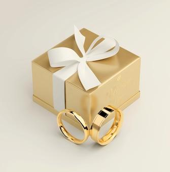 Rendu 3d d'une boîte cadeau en or avec un ruban blanc et des anneaux en or