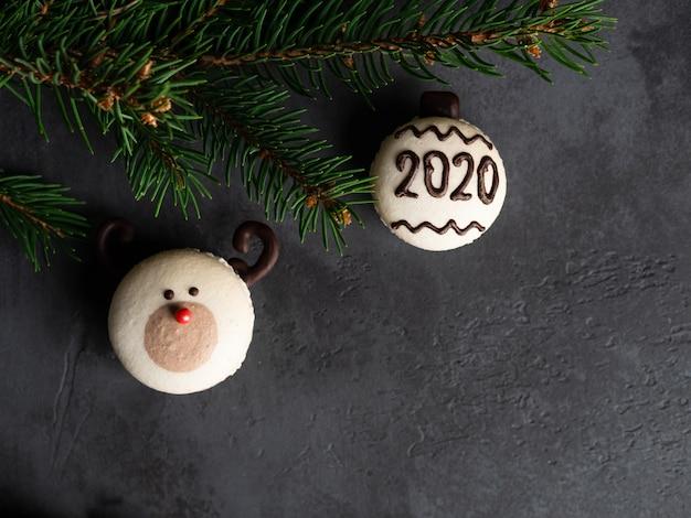 Renne au nez rouge macaron et macaron avec numéro 2020 avec brances de sapin sur fond noir foncé. carte de noël et nouvel an