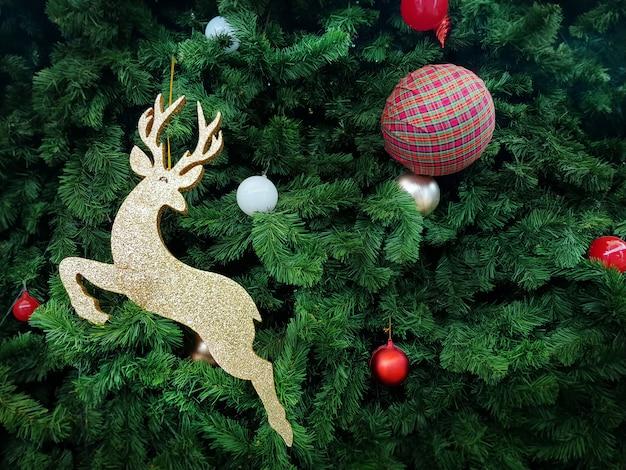 Renne doré et boules décorées sur l'arbre de noël vert