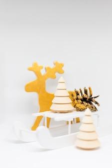 Renne jouet, traîneau de noël en bois, arbre de noël sur blanc