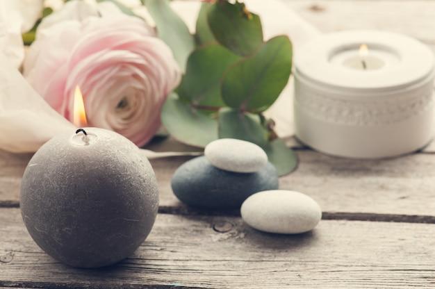 Renoncule rose, cailloux et bougies allumées