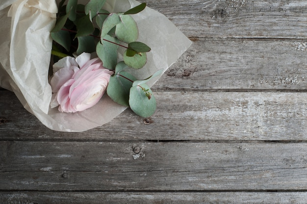 Renoncule rose sur fond en bois