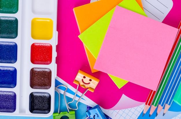 La rentrée scolaire avec des accessoires scolaires - peintures, crayons, cahiers, ciseaux, marqueurs