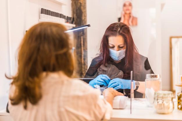 Réouverture de l'entreprise après la pandémie de coronavirus. manucure et pédicure spéciales avec mesures de sécurité pour un travailleur latina. salon de beauté covid-19
