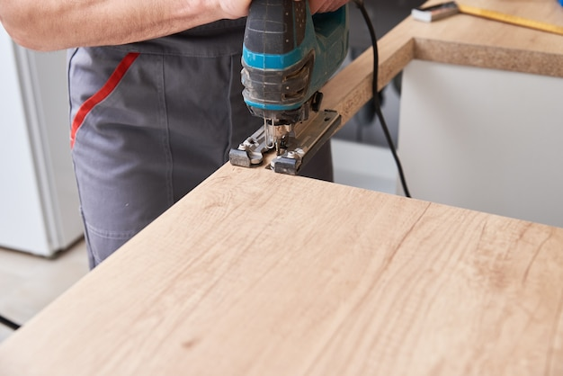 Réparateur à l'aide d'une scie sauteuse électrique. lieu de sciage pour l'installation de plaques à gaz dans un plan de travail