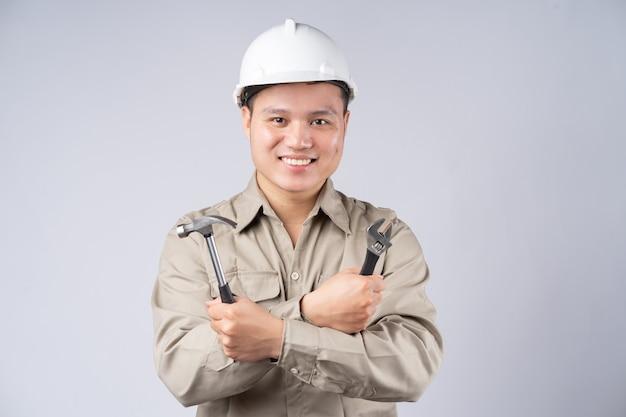 Réparateur asiatique debout avec les bras croisés sur fond gris