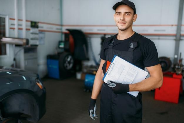 Le réparateur automobile en uniforme détient le rapport d'inspection, le service des pneus.