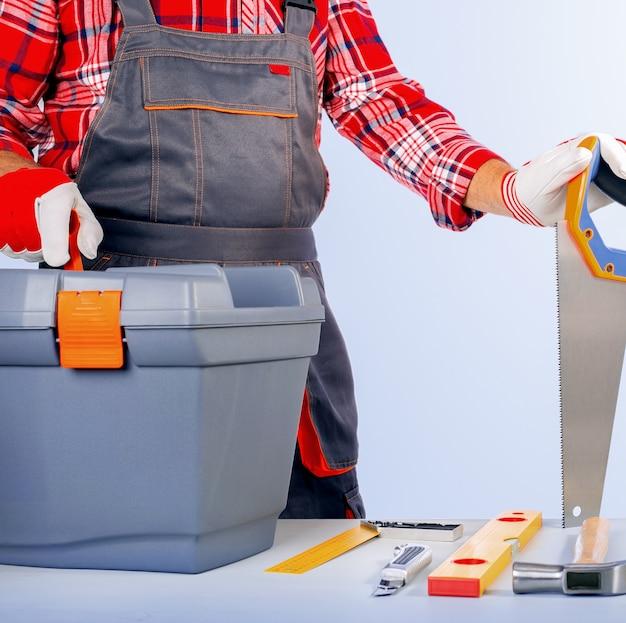 Réparateur avec boîte à outils contre le mur gris.