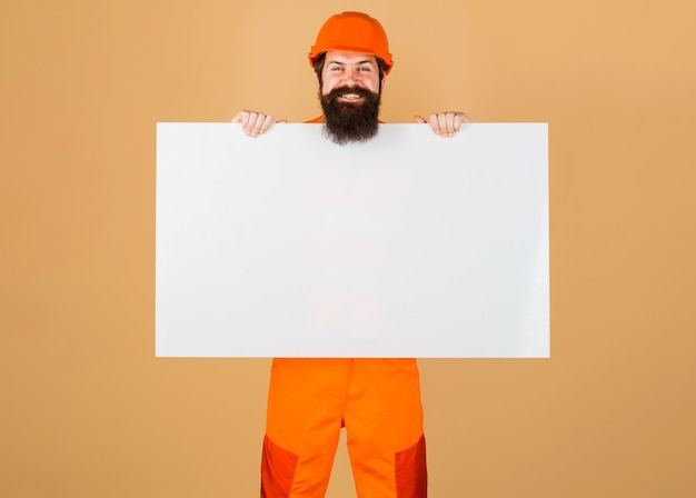 Réparateur en casque avec bannière publicitaire. un travailleur de la construction heureux dans un casque de protection montre un panneau vierge.