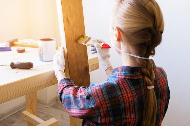 Réparateur, charpentier, travailleur acharné applique un vernis protecteur ou de la peinture sur une planche de bois.