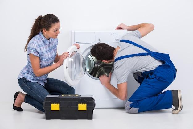 Réparateur est en train de réparer une machine à laver pour femme au foyer.
