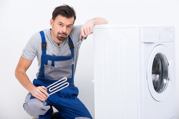 Réparateur fatigué est en train de réparer une machine à laver.