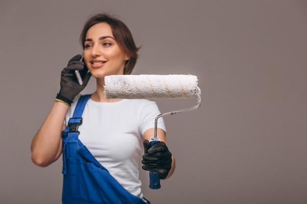 Réparateur de femme avec rouleau de peinture isolé parlant au téléphone