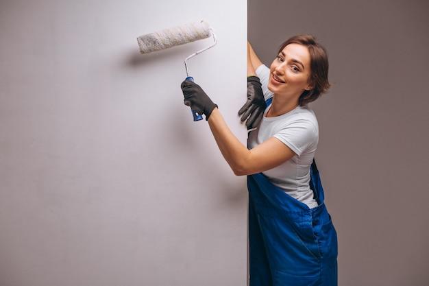 Réparateur de femme avec rouleau de peinture isolé