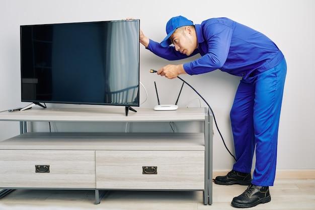 Réparateur installant un téléviseur
